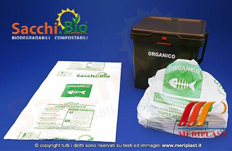 Dimostrazione della busta compostabile chiusa e riempita di materiale organico da smaltire e bidone dell'umido pulito - SACCHI.BIO